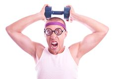 Nerd in glasses with dumbbell trains Royalty Free Stock Image