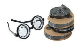 Nerd Glasses and Movie Reels. Reels of antique movie film with a set of nerd glasses - path included royalty free stock image