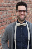 Nerd Guy With Glasses, Bow Tie, and Brick Wall Background Stock Photo