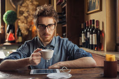 Nerd guy with tablet at the bar Royalty Free Stock Image