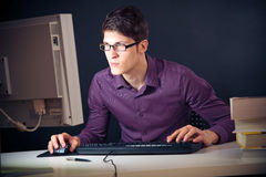 Nerd And His Computer. Young man with glasses sitting in front of his computer stock photos