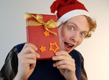Nerd holding xmas present. A weird nerd showing an xmas present with eyes wide open Royalty Free Stock Photo