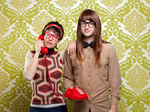Nerd humor couple talking vintage red phone. Funny nerd humor couple talking retro vintage red telephone on wallpaper stock photography