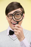 Nerd with magnifying glass. Young nerd man holding magnifying gl Stock Images