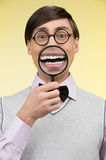 Nerd with magnifying glass. Young nerd man holding magnifying gl Royalty Free Stock Image