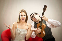 Nerd man boyfriend play ukulele love song for his girlfriend for valentine day Stock Images