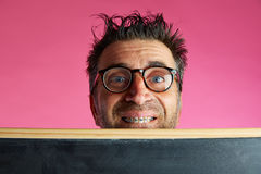Nerd man crazy behind blackboard funny gesture Royalty Free Stock Photography