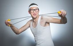 Nerd man doing gym. Loony skinny man exercise with expander doing fitness - training, isolated on gray white background stock images