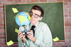 Nerd man holding earth world globe in classroom Stock Photography