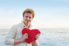 Nerd man holding felt heart near the sea Royalty Free Stock Photo