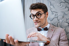Nerd man holding laptop and making funny face Royalty Free Stock Photos