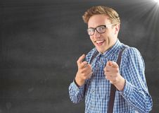 Nerd man pointing against grey wall with flare Stock Photo