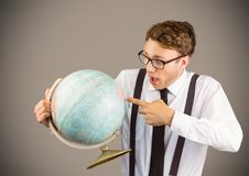 Nerd man pointing at globe against brown background Royalty Free Stock Photography