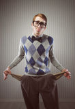 Recession. Nerd man stands holding his pockets out showing that he has no money royalty free stock photography