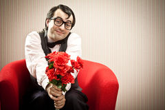 Nerd man wait his love on red armchair with flower gift Royalty Free Stock Photos