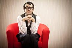 Nerd man wait on red armchair Stock Photo