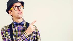 Nerd maschio nei punti degli occhiali con il pollice sullo spazio della copia per il vostro contenuto di pubblicità Nerd o geek d immagine stock libera da diritti