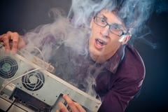 Nerd med rök som kommer ut ur hans PC royaltyfria foton