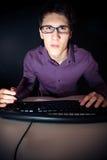 Nerd och hans dator arkivfoto