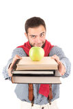 Nerd posing with books and apple. Young nerd student posing with books and apple isolated in a white background Royalty Free Stock Images