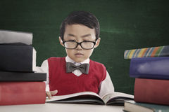 Nerd pupil reads book royalty free stock image