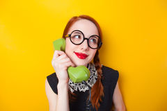 Nerd redhead girl. Redhead girl with green phone on yellow background Stock Images