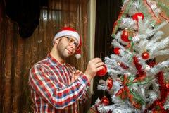 Nerd in santa hat decorate christmas tree Stock Images