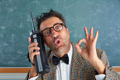 Nerd silly private investigator retro walkie talkie. Nerd silly private investigator with retro walkie talkie on teacher balckboard royalty free stock photo