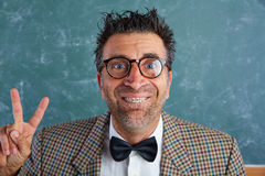 Nerd silly retro man with braces funny expression. Nerd silly retro man teacher with braces funny expression winner victory finger gesture Stock Photography