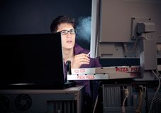 Young Man Spending His Night With Computers. Nerd sitting in front of his computers all night long stock photo