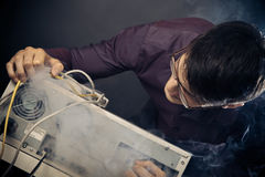 Nerd With Smoke Coming Out Of His Pc. Photo of nerd with smoke coming out of his pc Stock Photos