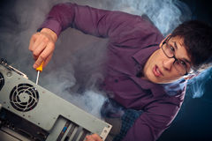 Nerd With Smoke Coming Out Of His Pc. Photo of nerd with smoke coming out of his pc Stock Images