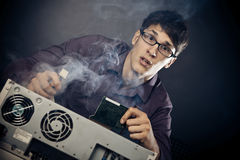 Nerd With Smoke Coming Out Of His Pc. Photo of nerd with smoke coming out of his pc Royalty Free Stock Images