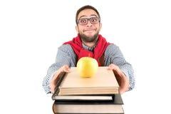 Nerd som poserar med böcker och äpplet arkivbilder