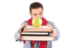 Nerd som poserar med böcker och äpplet royaltyfria bilder