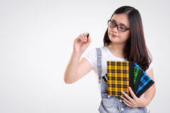 Nerd student gestures writing on screen. Nerdy school girl gestures writing on the screen with a pen, isolated on white background royalty free stock photos