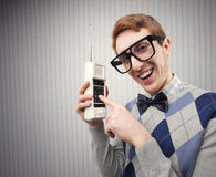 Nerd student. With an old mobile phone royalty free stock photography