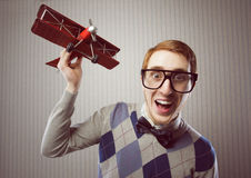 Nerd student. Playing with a tin airplane royalty free stock images