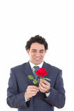 Nerd in a suit holding a rose with a funny expression on his fac Stock Photography