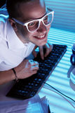 Nerd surfing internet at night time Stock Images