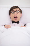 Nerd terrorizzato. Il nerd spaventato che si trova sul letto e che esamina è venuto fotografie stock