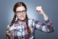 Nerd Woman with Gamepad. Nerd Woman with Braid Playing Videogames with a Joypad Royalty Free Stock Image