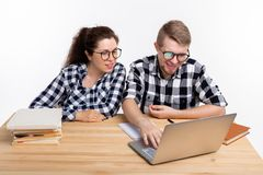 Nerds, geek, bespectacled and funny people concept - funny student couple in glasses sitting at the table.  royalty free stock photos