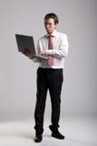 Nerdy affärsman som rymmer en bärbar dator Royaltyfri Bild