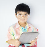 Nerdy Asian boy is holding a tablet isolated royalty free stock image