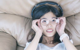 Nerdy Asian girl with glasses is listening to music royalty free stock images