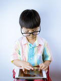 Nerdy Asian kid is playing education game on tablet. On white background Royalty Free Stock Images