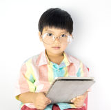 Nerdy Asian kid is studying on tablet. On white background Stock Image