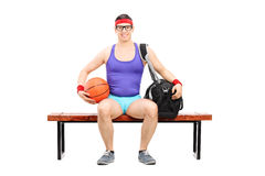 Nerdy athlete holding a basketball seated on a bench stock photos