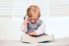 Nerdy behandla som ett barn pojken som läser en bok Royaltyfri Fotografi